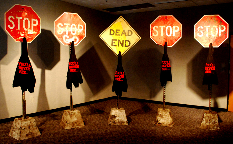Steel, concrete, road signs, embroidered black hoodies, and acrylic, five units at 106 x 30 x 19 inches, 2013.